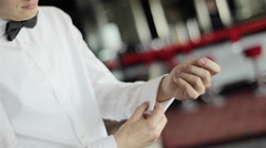 Man wearing bow tie puts cufflinks on sleeves of his white shirt. Close-up Stock Footage