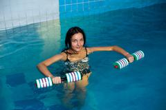 Attractive girl trains in aqua aerobics Stock Photos