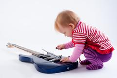 Little girl playing with guitar - stock photo