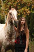 amazing girl standing next to the appaloosa horse - stock photo