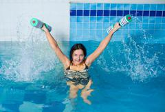 Pretty girl doing aqua aerobic exercise - stock photo