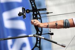 bow and arrow in the hands of an archer - stock photo
