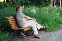 elder lady on park bench - stock photo