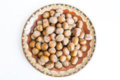 Unpeeled hazelnuts plate Stock Photos