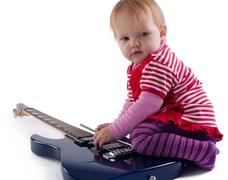 Little girl playing with guitar Stock Photos