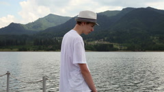 Mindful young man, unhappy teenage boy, lake water, mountain peaks Stock Footage