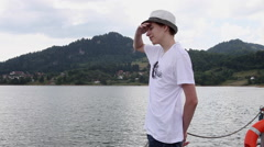 Teenager looking at lake water, mountain, woods, vacation, beautiful nature - stock footage