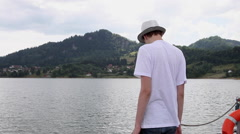 Depressed teen boy, thoughtful kid, suicide, sadness, lake water, mountain - stock footage