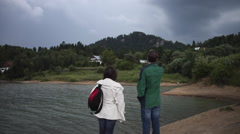 Tourists in thunderstorm with dark clouds and bad weather at mountain lake woods Stock Footage