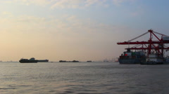 Sailing cargo ship and container port at sunset Stock Footage