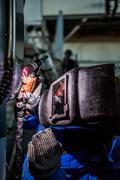 Man welding with reflection of sparks on visor. Hard job Stock Photos