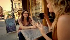 Two women sitting at outdoor table at cafe talking and drinking beverages Stock Footage
