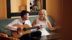 Groom playing guitar for bride Stock Footage