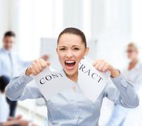 serious businesswoman tearing contract - stock photo