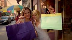 two women standing outside store smiling holding up shopping bags - stock footage