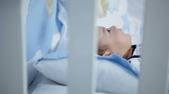 Baby in diaper lying in his crib at home in bedroom Stock Footage