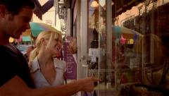 Man and woman looking in store window shopping Stock Footage