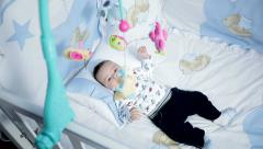 Baby in diaper playing with mobile in his crib at home in bedroom Stock Footage