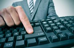 Stock Photo of businessman pressing the intro key of a computer keyboard