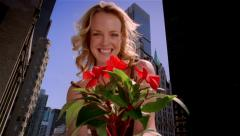 Low angle medium shot woman holding flowering plant Stock Footage