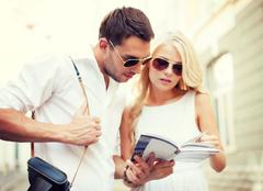 couple with tourist book in the city - stock photo