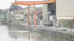 Truck loading raw materials into a river port - stock footage
