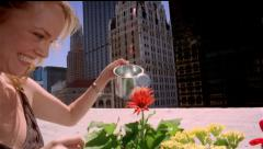 Woman watering flowers on rooftop / New York City Stock Footage