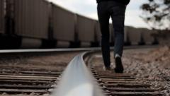 Hooded Person Walks Along Train Tracks - stock footage