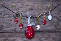 Many red and white easter eggs and one big egg hanging on line Stock Photos