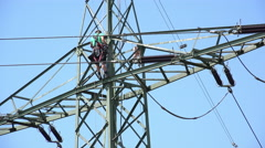 Man on power line securing harness 4k Stock Footage