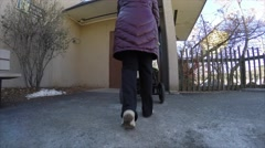 A mother walks son in stroller around zoo Stock Footage