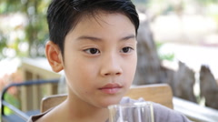 Young Asian child drinking a glass of water . Stock Footage