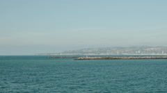 Parallel distant shot of jetty's from ocean  - stock footage