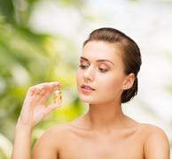 Beautiful woman showing bottle with golden dust Stock Photos