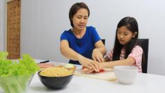 Asian daughter helping mother to slice up vegetables in kitchen Stock Footage