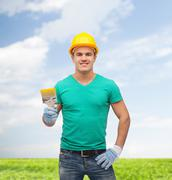 Stock Photo of smiling manual worker in helmet with paintbrush