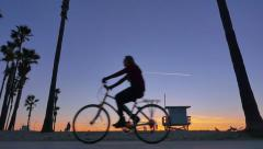 Bicyclists cycle at sunset as silhouettes between Santa Monica and Venice Beach Stock Footage