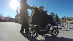 Mother walks toddler in a stroller around the zoo Stock Footage