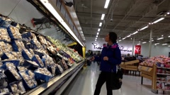 Woman selecting mushroom in grocery store Stock Footage