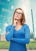 Happy woman in black eyeglasses dreaming Stock Photos