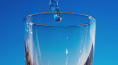 Blue water is flowing into the glass forming bubbles and splashes Stock Footage