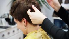 Hairdresser styling a short haired woman. Stock Footage