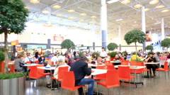 People have a rest and eat in cafe of a fast food in big shopping center Stock Footage