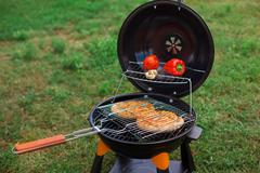 Fresh meat and vegetables on outdoor grill Stock Photos