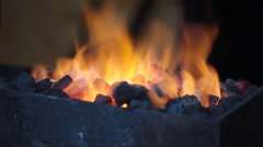 Bright flame of fire burns in a forge horn, the smith nippers gets hot coals - stock footage