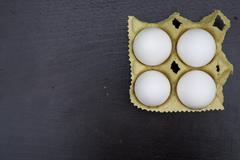 Four white chicken egg in the carton box Stock Photos