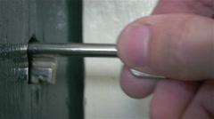 A close up of turning a key in an old wooden door. - stock footage