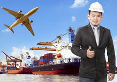 working man and commercial ship on port and air cargo plane flying above use  - stock photo