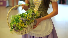 Unrecognizable girl in a beautiful dress with apron holding a basket of flowers Stock Footage