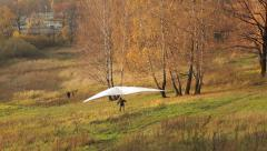The man on the old glider runs up, takes off and after a short flight landing Stock Footage